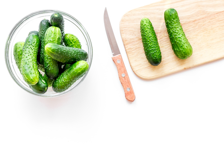 Make salad with fresh cucumbers. Vegetables on cutting board near knife on white background top view copyspace