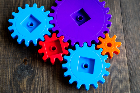 colorful gears for ideal team work technology wooden table background top view