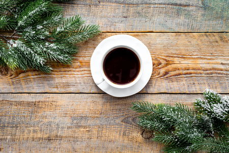 Christmas evening. Cup of coffee near spruce branch on rustic wooden background top view copyspace