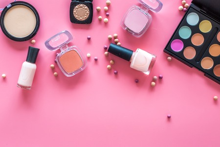 Decorative cosmetic set for natural makeup on pink background top view.