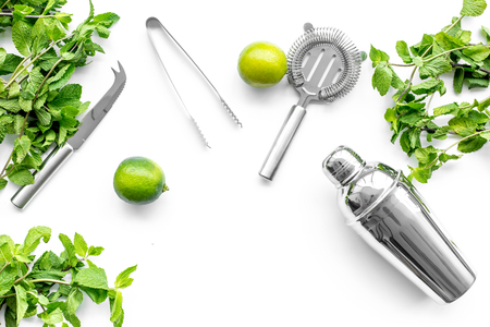 Make mojito cocktail with lime and peppermint in shaker. White background top view copyspace