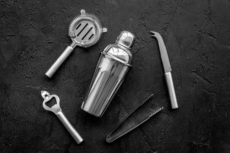 Instruments bartender. Shaker, strainer on black background top view