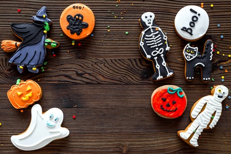 Cook halloween gingerbread cookies with witch, skeleton, ghost. wooden background top view copyspace