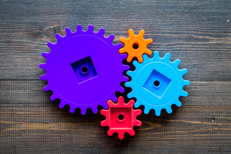 Moving forward concept, ideal operating principle with gears and wheels on wooden desk background top view mock up Stock Photo