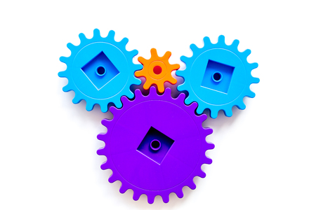 Bright gears for great technology of team work and correct mechanism on white table background top view