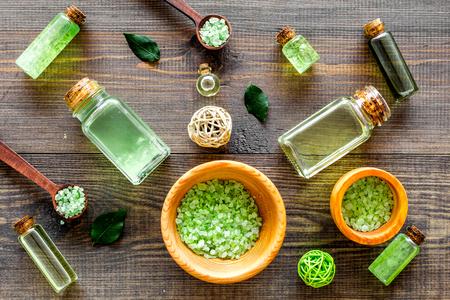 Organische schoonheidsmiddelen met theeboomolie en kuuroordzout op donker houten achtergrond hoogste meningspatroon Stockfoto