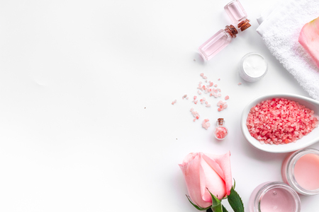 Spa products with rose oil. Cream, lotion and salt on white background top view.