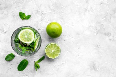 Glass of mojito, lime, mint on grey stone background top view. Banco de Imagens