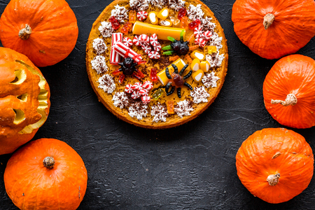 Halloween tradition. Pumpkin pie and pumpkin with scary face on black background top view. Stock Photo