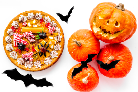 Tradición de Halloween. Pastel de calabaza y calabaza con cara de miedo en la vista superior de fondo blanco.