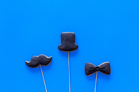 Happy Fathers day cards. Black tie, mustache and hat cookies. Blue background top view.
