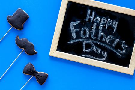 Words happy Fathers day written on blackboard. Black tie, mustache and hat cookies. Blue background top view. Stock Photo