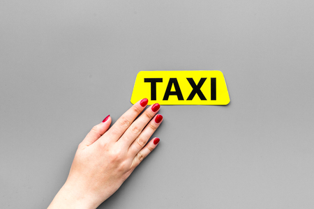 Women hand touch taxi label. Grey background top view.