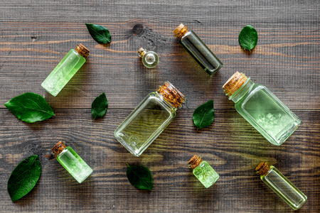 Pattern with skin care products with tea tree oil in bottles on dark wooden background top view Stock Photo