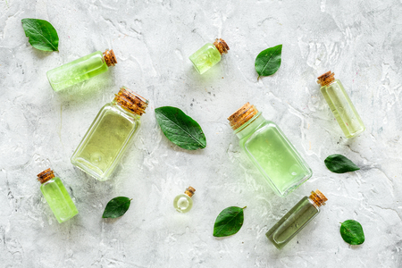 Skin care products with tea tree oil in bottles on grey stone background top view.