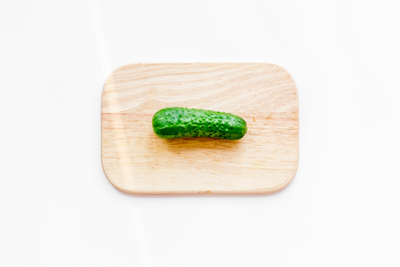 Make salad with fresh cucumbers. Vegetables on cutting board on white background top view.