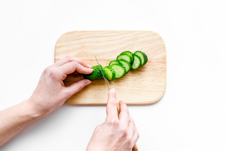 Hands cut cucumbers for salad. White background top view.