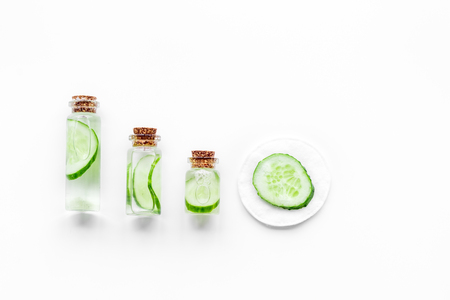 Fresh organic cosmetics with cucumber. Lotion on white background top view.