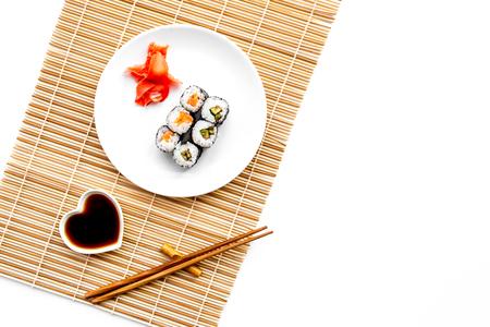 스시 롤 연어와 아보카도 간장, 젓가락, 흰색 배경에와 사비와 함께 접시에.
