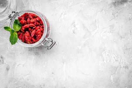 灰色の背景の上面にガラスの瓶に室伏の果実を乾燥させた。