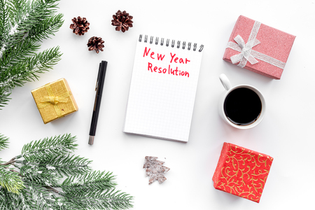 New year resolution. Notebook among gift boxes and spruce branch on white background top view. Zdjęcie Seryjne