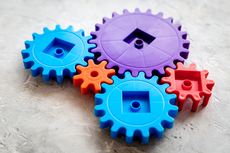 colorful gears for ideal team work technology on stone table background