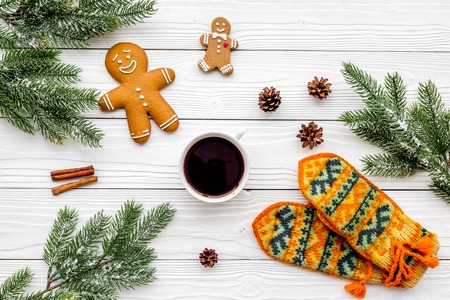 Christmas evening. Gingerbread man and knitten mittens near spruce branch on white wooden background top view. Stock Photo