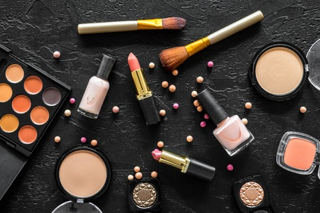 Beige and nude tones cosmetics for natural makeup on black background top view.