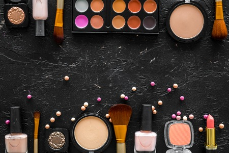 Bulk cosmetics beige and nude colors on black background top view.