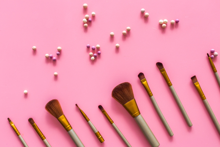 Natural makeup. Ball blushers and brushes pattern on pink background top view.