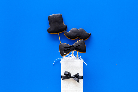 Happy Fathers day cards. Black tie, mustache and hat cookies in gift. Blue background top view.