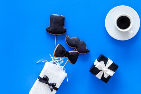Happy Fathers day cards. Black tie, mustache and hat cookies and gift. Blue background top view.