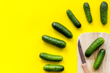 Make salad with fresh cucumbers. Vegetables near knife on cutting board on yellow background top view.