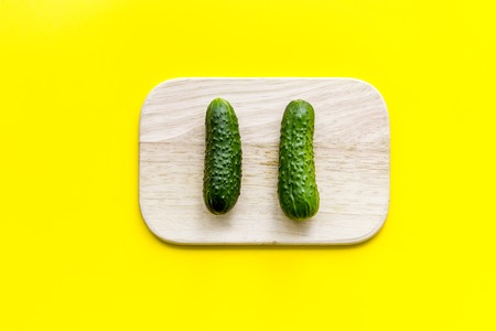 Make salad with fresh cucumbers. Vegetables on cutting board on yellow background top view.