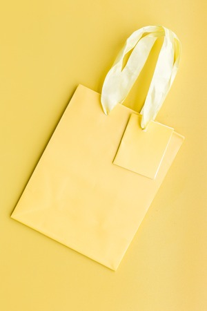 Yellow bright shopping bag on yellow background top view.