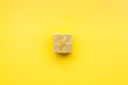 Shopping and sales. Gold gift box on yellow background top view. Stock Photo