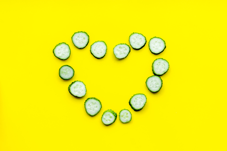 Sliced cucumber in shape of heart on yellow background top view.