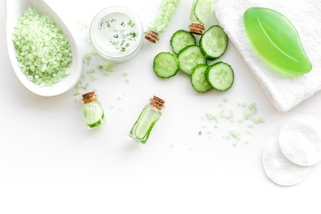 Fresh organic cosmetics with cucumber. Cream, lotion, spa salt on white background top view.