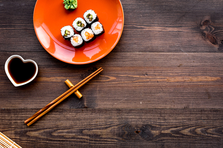 Sushi roll with salmon and avocado on plate with soy sauce, chopstick, wasabi on wooden table background.