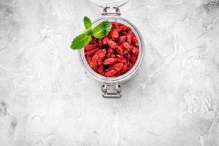 Dried goji berries in glass jar on grey background top view.