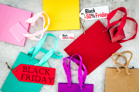 Black friday labels near paper shopping bag on grey background top view. Stock Photo