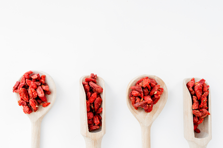 Wooden spoons with dried goji berries on white background top view.