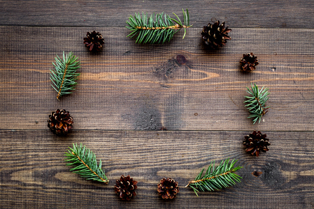 Spruce branch and pinecone pattern on wooden background top view.