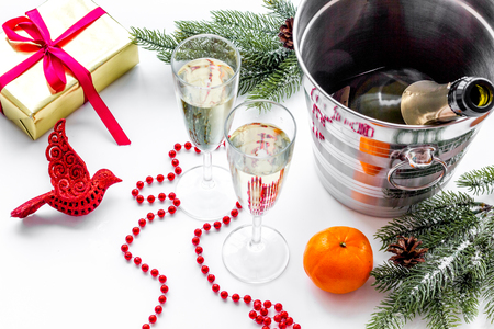 New Year 2018 background. Champagne in bucket, glasses with beverage, spruce branch and decoration on white background.