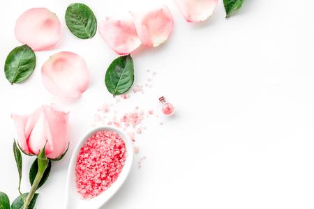 Modèle avec des cosmétiques à l'huile de rose. Pétales de rose, sel de spa sur la vue de dessus de fond blanc.