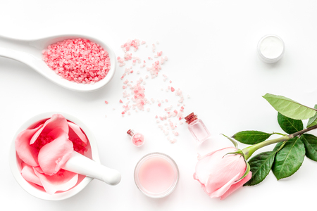 Make cosmetics with rose  oil. Mortar with rose petals and pestle on grey stone background top view.