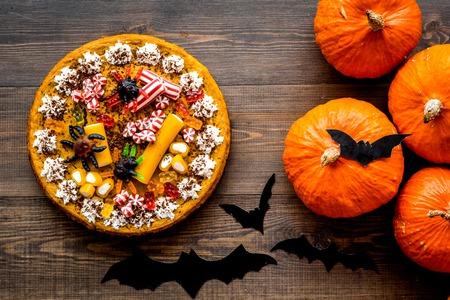 Halloween tradition. Pumpkin pie on wooden background top view.