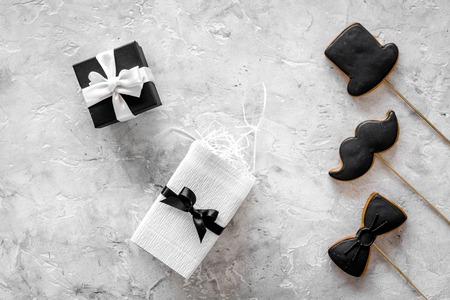 Birthday gift for men. Wrapped box, cookies in shape of black tie, mustache, hat. Grey background top view.