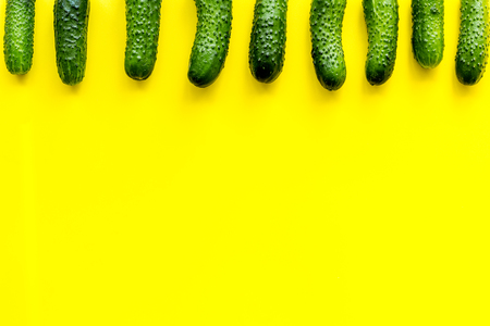 Fresh cucumbers pattern on yellow background top view.