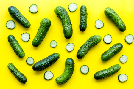 Fresh cucumber pattern on yellow background top view.